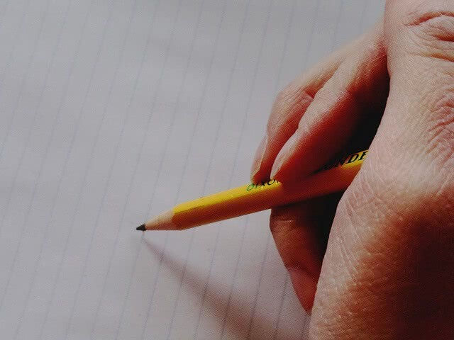 A hand holding a pencil ready to write on lined paper.