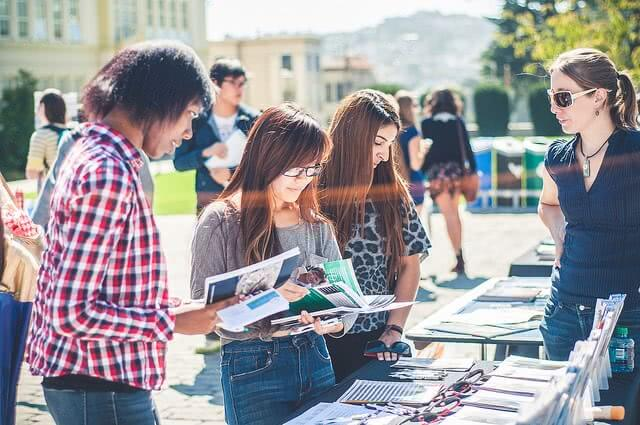 Students looking at the magazines during study abroad fair.