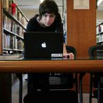 A student in the library starring at her black mac laptop.