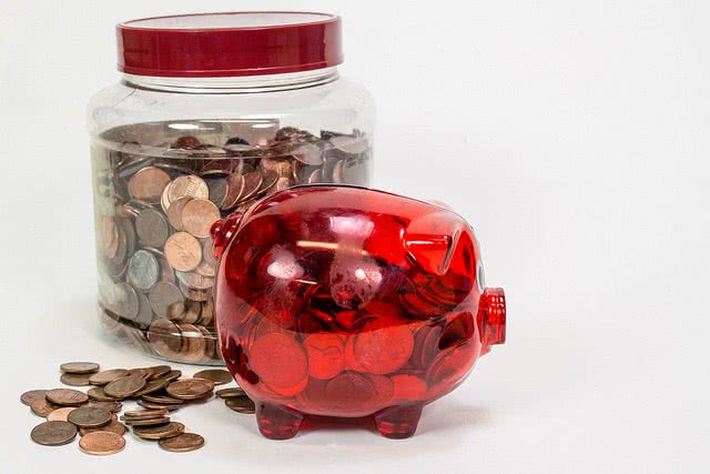 A piggy bank and jar full of coins inside.