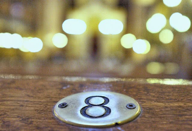 Golden plate number 8 screwed on a wooden table.