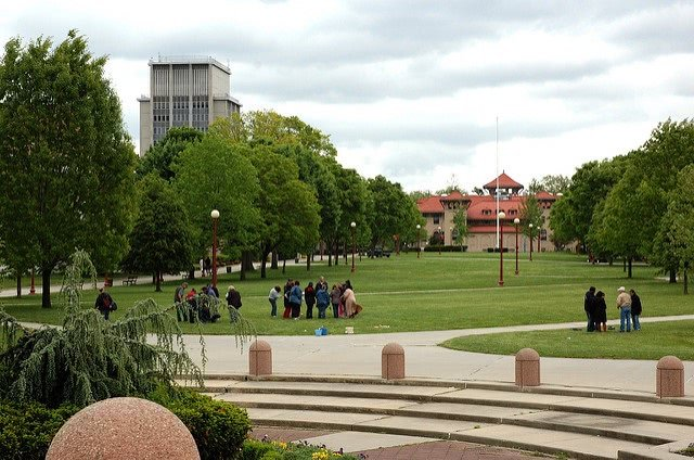 Students gathering in The Queens College campus field.