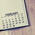 A high school student's calendar planner sitting on a wooden desk.