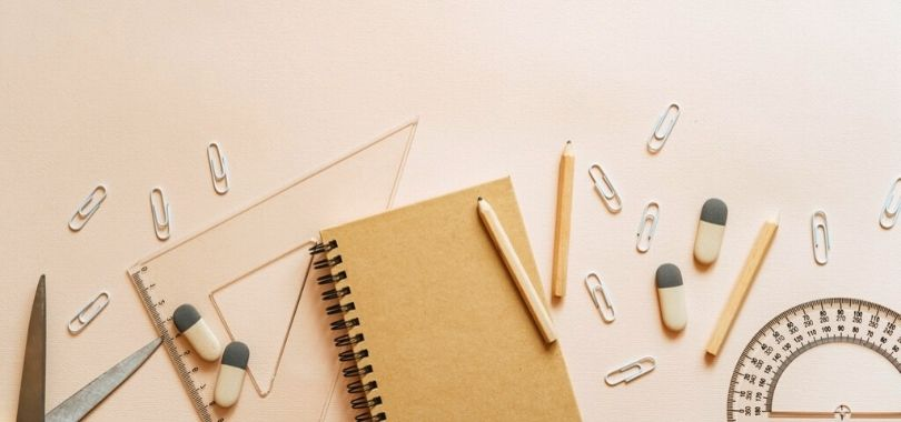 A notebook, pencils, paperclips and protractors scattered on a desk.