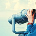 A person looking through a pair of binoculars.