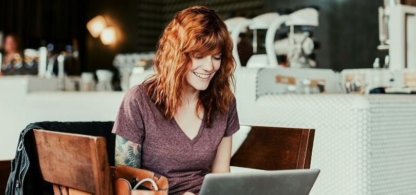 College student smiling as she works on her laptop in a coffee shop.