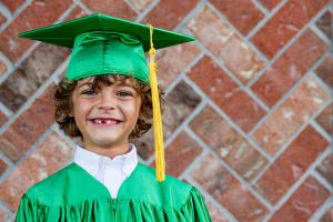 Young boy in grad cap and gown - many families wonder about the best 529 plans