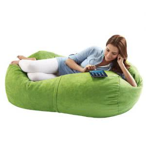 Student lying in her lime Jaxx Sofa Saxx bean bag chair while looking at an iPad. Click to view its Amazon page.