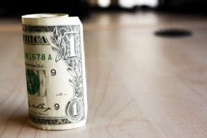 Rolled dollar bill - save money on the cost of college education