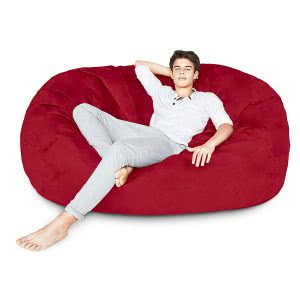 A student lying in a red Lumaland bean bag lounger. Click to view its Amazon page.