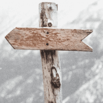 A wooden arrow on a post pointing to the left.