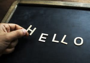 """A student holding the letter H, spelling out """"hello."""""""