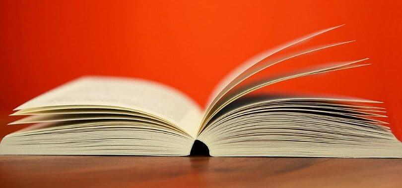 An open book on a desk with a red background.