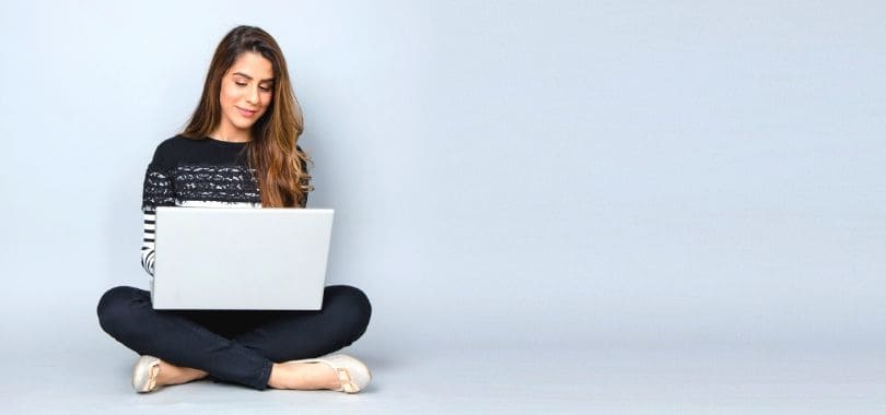 A person sitting on the ground with a laptop in their lap.