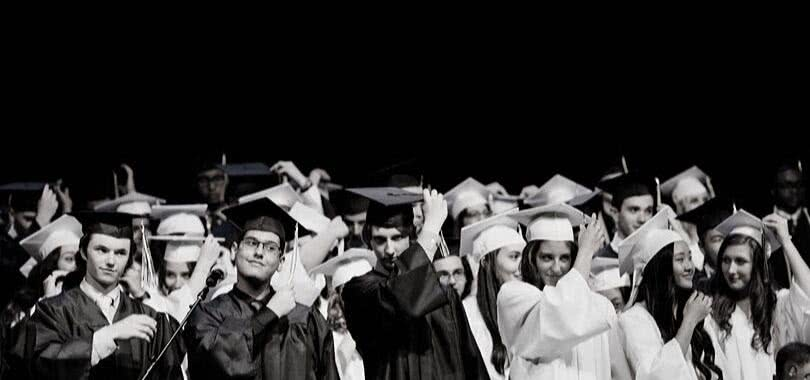 High school students at graduation, moving their tassels on their graduation caps.