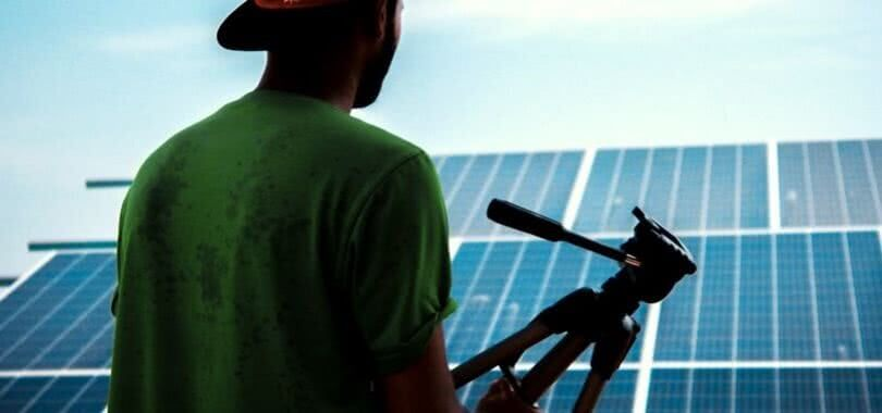 A solar photovoltaic installer holding a tool and looking out over solar panels.
