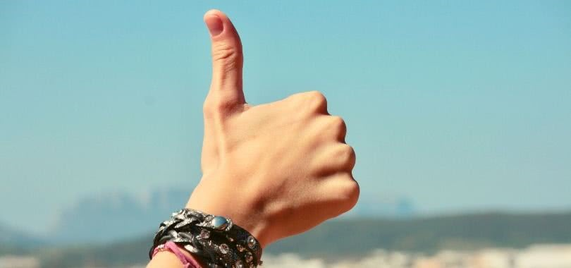 A student's hand with leather bracelets giving a thumbs up in the sky.