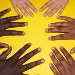 Three people of various races place their hands on a yellow table.