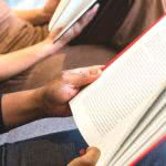 Two high school students reading books to prepare for a college entrance exam.