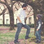 A father and young daughter standing beneath spring trees outside a college building.