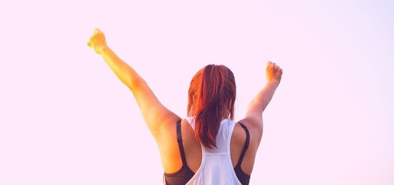 A high school student with her arms in the air doing a victory pose.