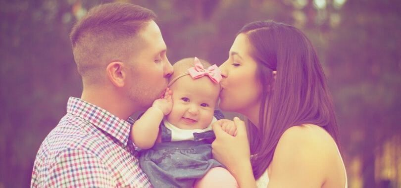 Parents kissing their baby's cheeks.