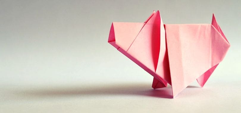 A pink origami pig standing on a gray surface.