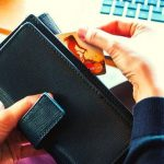 A person holding a wallet and pulling out a credit card.