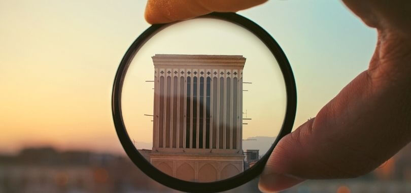 Magnifying glass over college building.