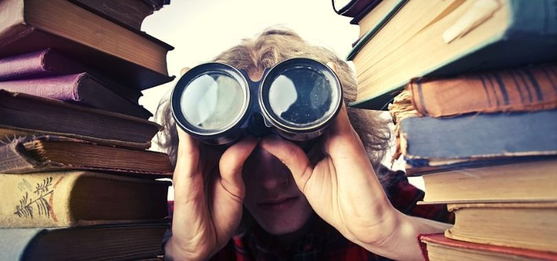 A college student surrounded by books and looking through binoculars for careers