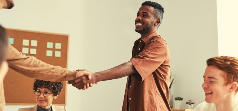student shaking hands with college official
