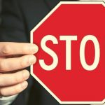 Suited man holds up a stop sign