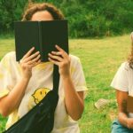 Two high school seniors reading outside during summer to prep for college.