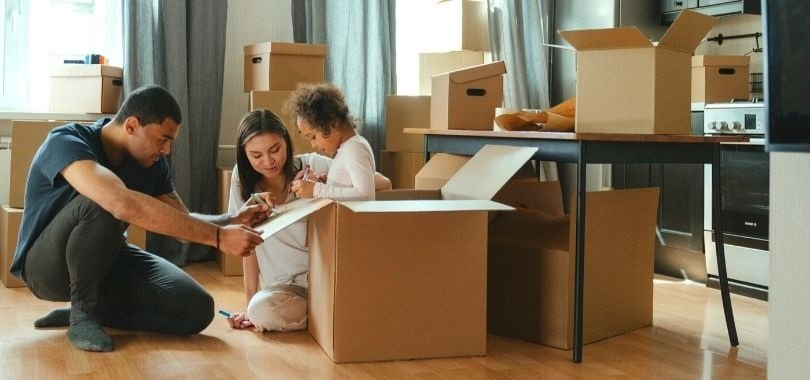 Parents playing in moving boxes with their daughter. They're thinking about 529 savings plans for her future education.