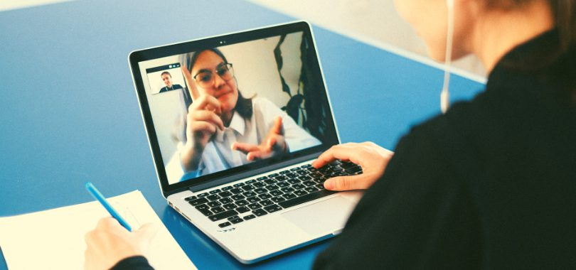 A student watches a professor on her laptop during an online class in her hybrid program.