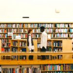 Two students standing in their liberal arts college library