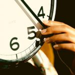 A student's hand reaches up to hold the minute-hand of a clock. They consider applying early decision for multiple schools.